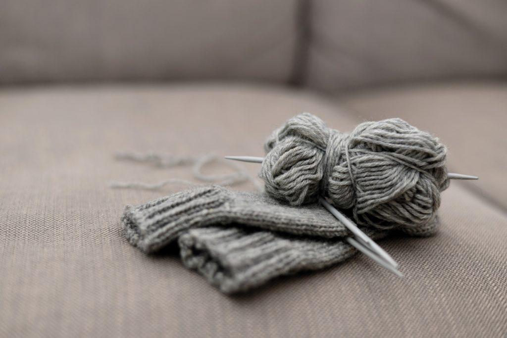 Two mittens in the process of being knit, left on the couch.